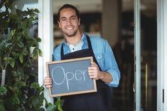 显示有开放标志的微笑的侍者画象黑板 免版税图库摄影