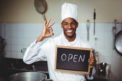 显示有开放标志的微笑的厨师黑板 库存照片