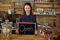 显示有开放标志的微笑的女服务员黑板在柜台 免版税图库摄影