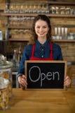 显示有开放标志的微笑的女服务员黑板在柜台 库存图片