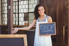 显示有开放标志的微笑的女服务员黑板 库存照片