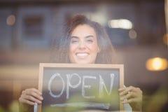 显示有开放标志的微笑的女服务员黑板 库存图片