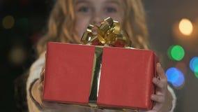 显示有弓的逗人喜爱的女孩大红色箱子入提出圣诞节的照相机礼物 影视素材