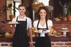 显示有款待的微笑的侍者和女服务员板材 免版税库存图片