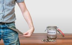 显示有硬币的人口袋作为没有金钱标志和瓶子 免版税图库摄影
