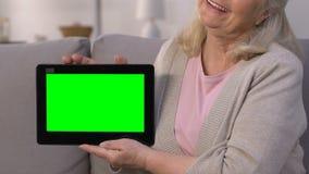 显示有绿色屏幕的微笑的年长夫人片剂,在网上快速地相信 影视素材