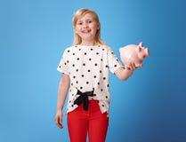 显示有膏药的愉快的现代孩子存钱罐在蓝色 免版税库存图片