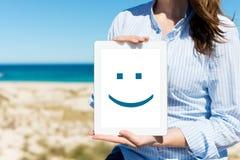 显示有兴高采烈的面孔的妇女数字式片剂在海滩 免版税库存照片