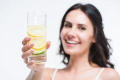 显示杯水的微笑的妇女用柠檬 免版税库存照片
