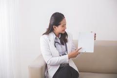 显示某事在片剂个人计算机的年轻亚裔女性医生和 库存照片