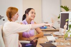 显示某事在计算机上的女实业家对女性同事 免版税库存照片