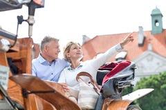 显示某事的中年妇女供以人员,当坐在马推车时 库存照片