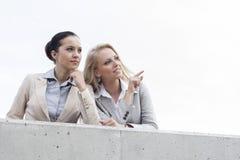 显示某事的低角度观点的愉快的年轻女实业家对同事,当站立在大阳台反对天空时 免版税库存照片