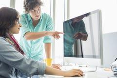 显示某事的创造性的商人对在台式计算机上的同事在办公室 免版税库存照片