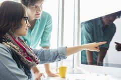 显示某事的创造性的女实业家对在台式计算机上的同事在办公室 图库摄影