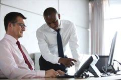 显示某事的商人对膝上型计算机的男性同事在办公桌 库存照片