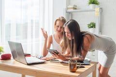 显示某事的女实业家对tablep个人计算机的同事在办公室 免版税库存照片
