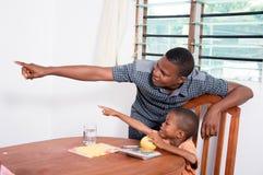 显示某事的爸爸对他的孩子 免版税库存照片
