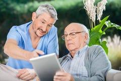 显示某事的男性护士对老人  免版税库存照片