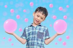 显示桃红色泡影的年轻亚裔男孩 免版税库存照片