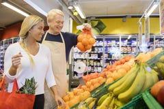 显示桔子的推销员对女性顾客在商店 免版税库存图片