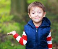 显示棕榈的小男孩 免版税库存图片
