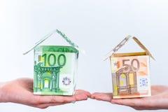 显示欧洲票据房子的两只手 免版税库存照片