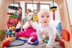 显示求知欲的逗人喜爱的女婴通过设法到达多彩多姿的玩具 免版税库存图片