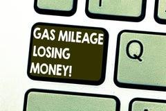 显示汽油里程丢失的金钱的文本标志 概念性照片漫长的路高气体燃料费用经济损失键盘键 库存图片