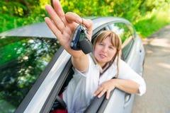 显示汽车的钥匙的愉快的司机 免版税图库摄影