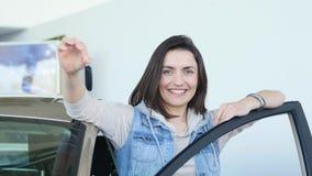 显示汽车钥匙和倾斜在车门的愉快的妇女司机 免版税库存照片