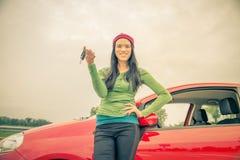 显示汽车钥匙的亚裔妇女 免版税库存图片