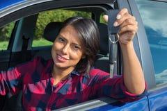 显示汽车钥匙的妇女通过开窗口 库存照片