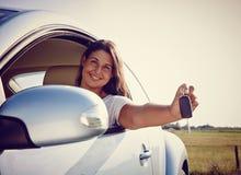 显示汽车钥匙的愉快的年轻汽车妇女 库存照片