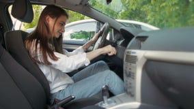 显示汽车钥匙的年轻逗人喜爱的愉快的妇女在得到驾驶执照以后 美丽的年轻驾驶的学生发动汽车在