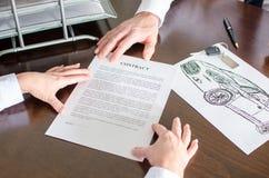 显示汽车购买契约的经销商 免版税库存照片