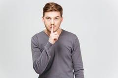 显示沈默姿态的灰色套头衫的英俊的年轻人 库存图片