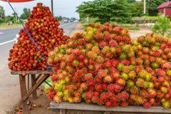 显示沿高速公路的待售新鲜的成熟红毛丹是Popu 免版税库存图片