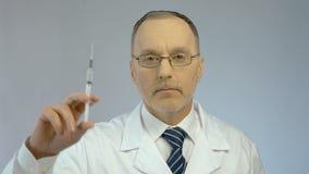显示注射器和细颈瓶的严肃的男性医生,准备做疫苗射入 影视素材