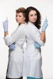 显示注射器的两位妇女外科医生画象  库存照片