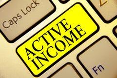 显示活跃收入的文本标志 概念性照片皇族薪金退休金金融投资打翻键盘黄色 免版税库存照片