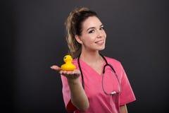 显示浴鸭子的可爱的夫人医生画象  免版税库存图片