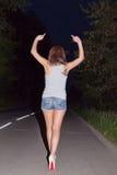 显示淫秽姿态的女孩在沿路的步行距离 免版税库存照片