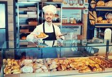 显示温暖的鲜美新月形面包的人面包师 免版税图库摄影