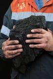 显示煤炭的团与赞许的煤矿工人反对黑暗 免版税库存图片