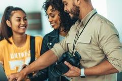显示照片的摄影师对他的在膝上型计算机的队 免版税库存图片