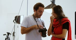 显示照片的男性摄影师对在数码相机4k的女性模型 股票录像