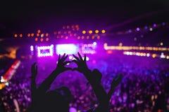显示爱的心形的手在节日 反对音乐会的剪影点燃背景 免版税库存图片