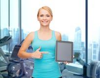 显示片剂个人计算机的微笑的运动的妇女在健身房 免版税图库摄影