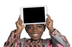 显示片剂个人计算机,赠送阅本空间的非洲男孩 库存照片